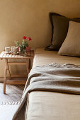 Pillows on bed with beakers and flowers on small wooden bedside table
