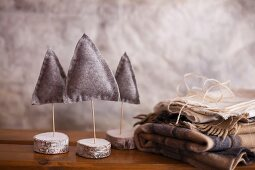 Three small felt Christmas trees next to folded woollen blankets
