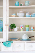 Colourful mugs and teapots in white cupboard