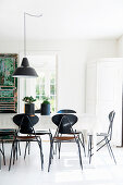 White dining table and black chairs on white wooden floor