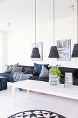 Pendant lamps above white coffee table and grey sofa with scatter cushions