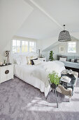 Bright bedroom in gray and white under the roof
