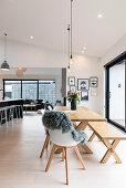 Holztisch mit Bank und Stühlen im offenen Wohnraum mit hoher Decke