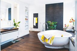 A designer bath tub in front of a bench in a cosy bathroom