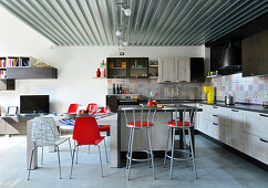 Designer chairs in kitchen and dining area of industrial loft apartment