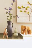 Wooden animal figures and ceramic vases on a sideboard