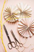 Papierrosetten, Scheren und gelb bemalter Zweig auf rosa Grund