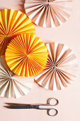 Gelbe und rosafarbene Papierrosetten neben einer Schere