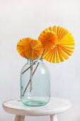 Sonnengelbe Papierrosetten auf Holzstäben in einem Einmachglas