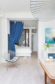 Klassikerstuhl vor Schlafbereich mit blauem Vorhang