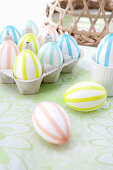 White Easter eggs with decorated colourful stripes