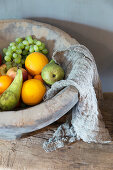 Fruit and cheesecloth in rustic terracotta bowl