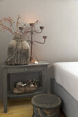Rustic accessories in shades of grey on small table next to bed