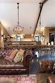 Vintage leather couch, long dining table and kitchen in converted barn