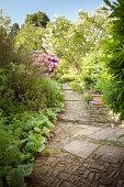 Natursteinweg mit Treppe führt durch dicht bepflanzten sommerlichen Garten