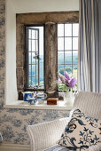 Cushion on wicker armchair in front of rustic stone window and toile de jouy wallpaper
