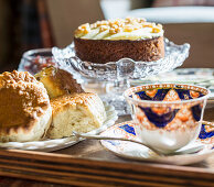 Pastries, cake and elegant teacup and saucer on table