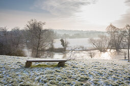 Bench with view of river in wintry landscape