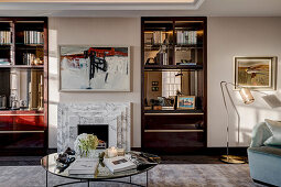 View across coffee table to fireplace with marble surround flanked by integrated shelves
