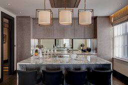 Kitchen island with marble worksurface and barstools