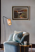 Armchair with scatter cushions between standard lamp and side table in front of painting on wall