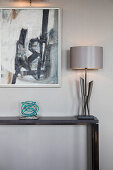 Silver lamp and ornament on console table below modern artwork on wall