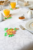 Hand-made fusion-bead coasters on table set for spring breakfast