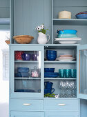 Blue lacquered display cabinet with dishes