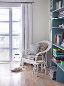 Rattan armchairs and stools next to blue bookshelf