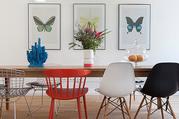 Various designer chairs around dining table in front of pictures of butterflies