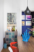 Blue sculpture of coral on dining table and view into corridor with blue wall