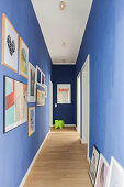 Gallery of pictures on blue walls in corridor