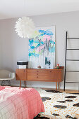 Abstract painting on top of retro sideboard in bedroom