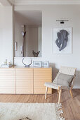 Easy chair and sideboard in front of aperture in grey interior wall