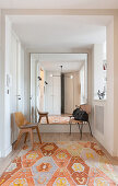 Large mirror on wall in hallway with kilim rug in shades of orange