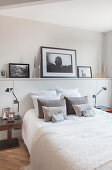 Pictures on ledge above bed in monochrome bedroom