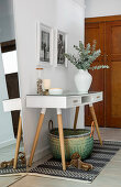 Lowboy and mirror leant against wall in white foyer