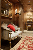 Baroque bench in opulent, candlelit hallway with wood panelling