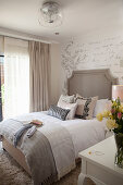 Double bed against wallpaper with pattern of French writing in elegant bedroom with feminine ambiance