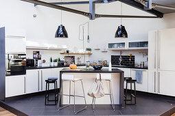 Island counter in open-plan kitchen on platform in open-plan interior