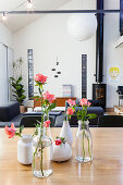 Vases of roses on dining table in front of log burner in lounge area