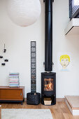 Log burner next to strip of glass bricks and low sideboard in loft apartment