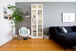 Reading corner, display case and dark sofa against grey wall