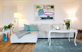 Helles Ecksofa, darüber moderne Kunst, weißer Couchtisch, Beistelltische und Stehlampe im Wohnzimmer
