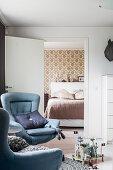 Two blue armchairs in front of open door leading into bedroom