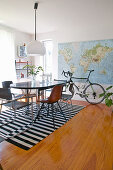 Table and chairs on black-and-white striped rug with bicycle in background below map on wall in dining room