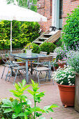 Garden furniture on summery terrace behind brick house