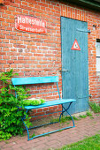 Blue garden bench against brick house with blue door and enamel sign