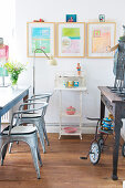Three pastel-coloured artworks and vintage accessories in dining room