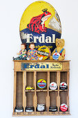 Enamel sign above old wooden shelves of dolls and shoe-polish tins